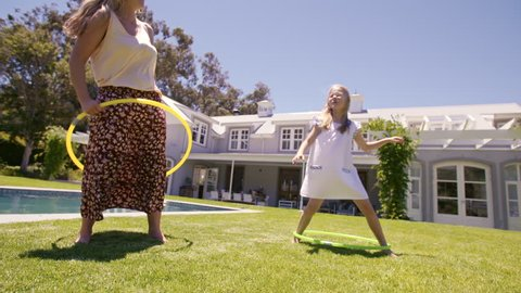 Woman and young girl outdoors using hula hoops and smiling. Mother and daughter playing with hula hoop in their backyard.