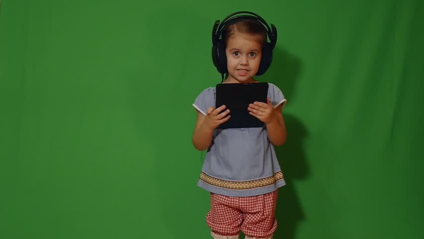 Kid girl in headphones reading on tablet computer | Shutterstock HD Video #1007646967