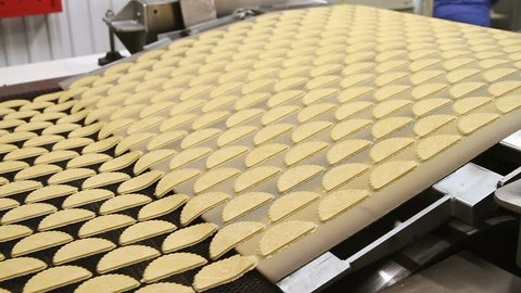 Dough for baking cookies. Forming dough for biscuits. Conveyor belt with biscuits in a food factory - machinery equipment. Production line of baking cookies. Conveyor with cookies.