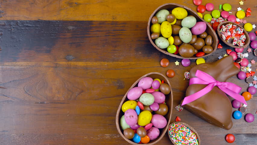 Happy Easter decadent chocolate background overhead with Easter eggs and candy on a rustic wood background with copy space timelapse.
