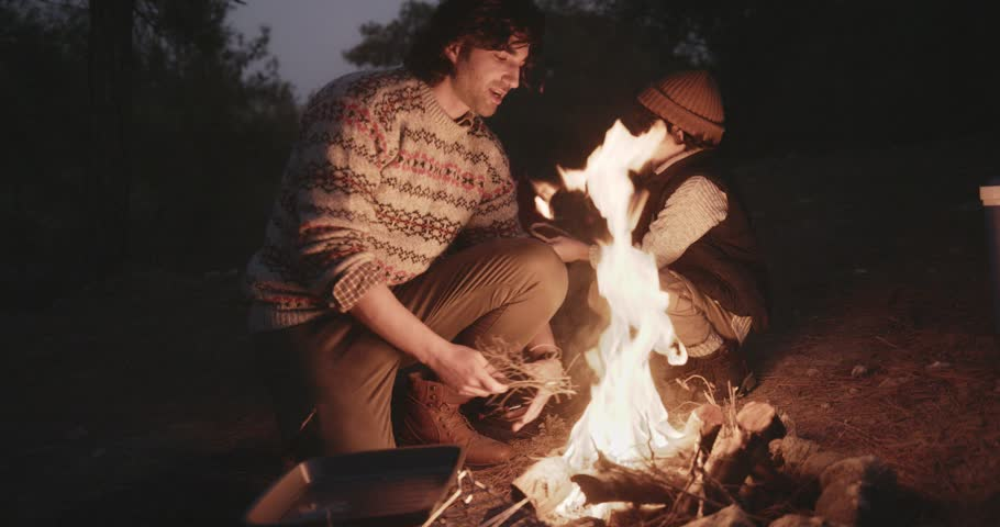Young father and son on winter forest camping adventure lighting campfire at night