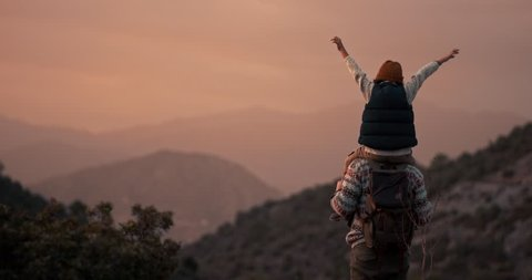 Successful father hiker standing on mountain peak looking at view with son on shoulders