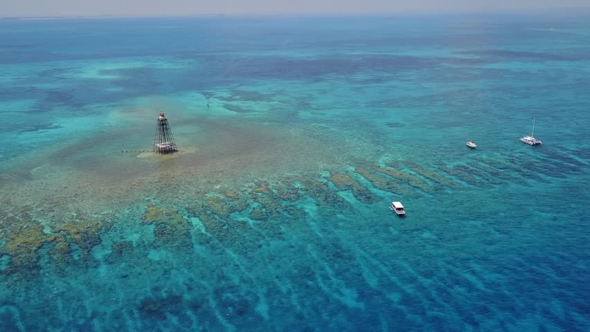 Aerial view of Sand Key LightHouse Reef outside of Key West Florida. Filmed from a DJI Mavic Pro on a warm sunny summer day. Part of John Pennekamp state park, it's a major tourist attraction for FL.