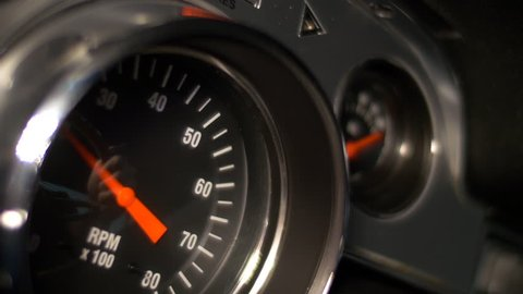 Tachometer of a classic muscle car reacts to hard accelerations by the driver, who is reflected in the glass.