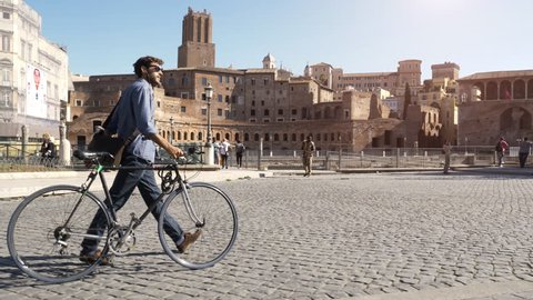 Young hipster man riding bike among ruins in roman forum imperial in Rome city centre on sunny day slow motion camera car