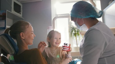 Girl, her mom and the dentist in the dental office, the stomatologist examining and consulting, daughter curious and docile