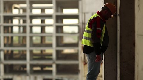 Stressed builder in hard hat stands on construction site and knocks his head against the concrete wall, self-condemnation and self-torture. Worker knocks his head against the wall