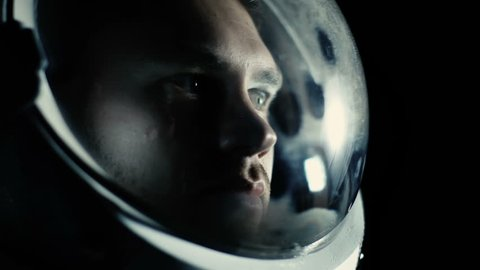 Portrait Shot of the Courageuos Astronaut Wearing Helmet in Space, Looking around in Wonder. Space Travel, Exploration and Solar System Colonization Concept. Shot on RED EPIC-W 8K Helium Cinema Camera