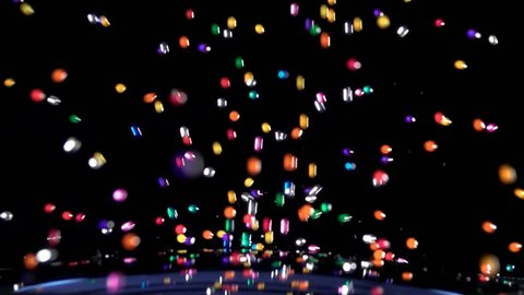 Colored balls falling and landing on ground against black background in slow motion / shot at 480fps