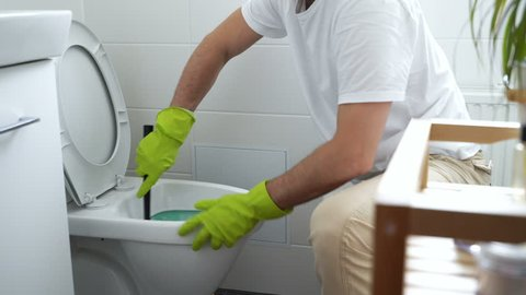 The man at work. Man with a rubber glove cleans a toilet bowl using means for cleaning