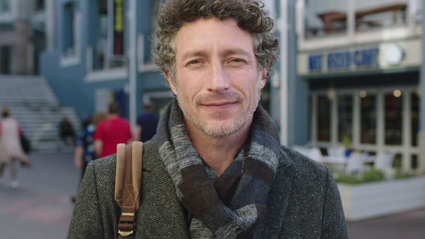 slow motion portrait of attractive mature caucasian man enjoying travel lifestyle smiling at camera in urban city wearing scarf relaxed commuting