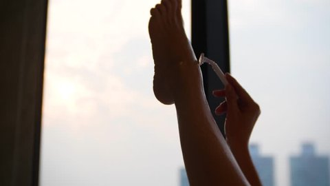 4k, female legs in the bathroom of the hotel room. woman shaves her legs in the bathroom on the background of a window overlooking the skyscrapers. close-up