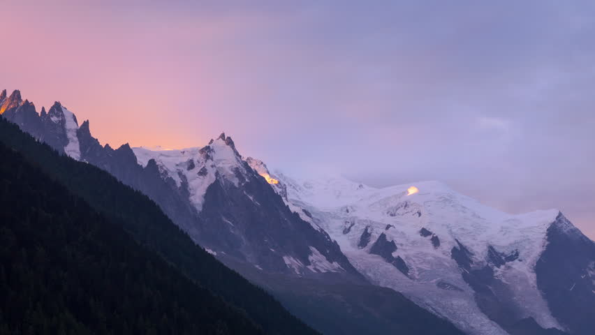 Picturesque timelapse of sunrise at the Mont Blanc range mountains with beautiful purple sky, view to the Aiguille du Midi peak, France.