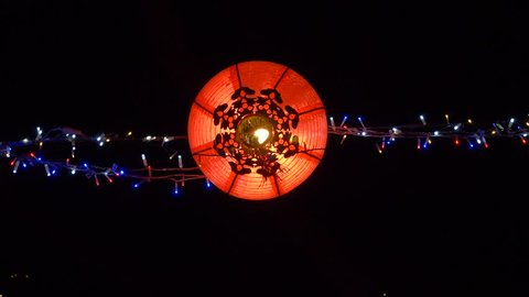 Bottom Up Shot of Chinese Lantern Hung on a String of LED Lights Swaying in the Night Breeze