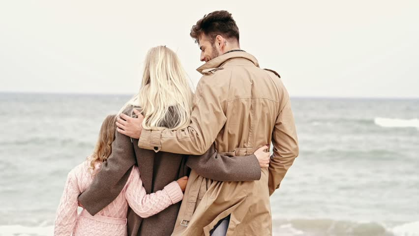 Back view of Young family with a little daughter standing near the beach together | Shutterstock HD Video #1007787307