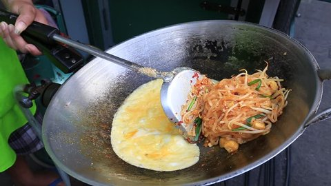Street food : thai man is cooking pad thai noodle with egg at night food market in island Koh Phangan, Thailand