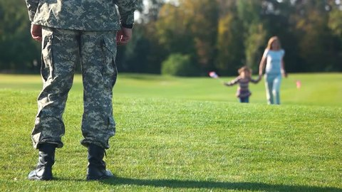 Happy mother and daughter running to the father, front view. Father came back home from the military mission. Back side view soldier in camo