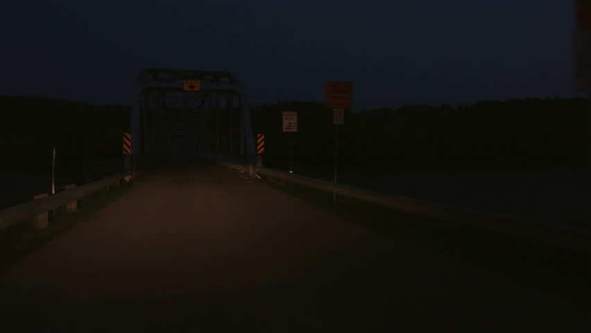 POV shot of driving across a steel girder bridge at night time.  Road on bridge is wood planks and headlights light up the bridge and road.