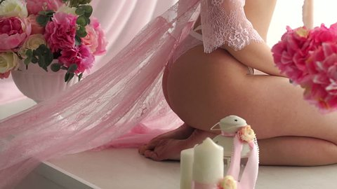 Close-up of sexy ass girl in lingerie and transparent pink negligee in the Studio against the background of flowers and candles.