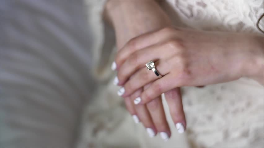 Female hands close up with silver golden ring diamond rack focus. Woman wear engagement wedding ring on finger polished nails lace dress worry before ceremony. Life of rich glamour wealth cinderella