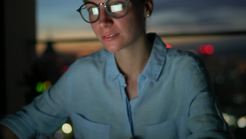 Young caucasian businesswoman in optical eye wear working late at office on laptop computer and having voice call talking about work.Female freelancer conversate with customer having deadline at night | Shutterstock HD Video #1007840557