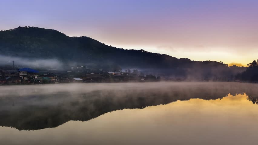 4k timelapes zoom out and pan  video of movement fog mist over lake with  mountain and morning light background  | Shutterstock HD Video #1007849317
