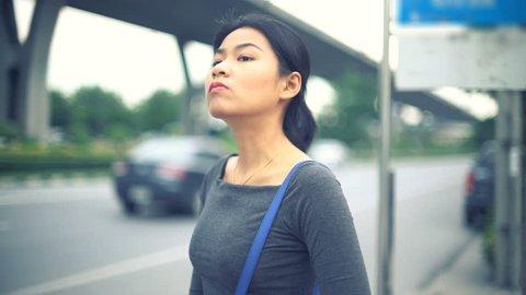 Young Asian Woman waiting at bus stop toned video 4k UHD (3840x2160)