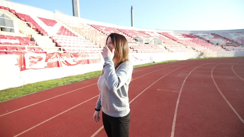 SLOW MOTION: Young sporty woman is having a laugh while standing at the running track.