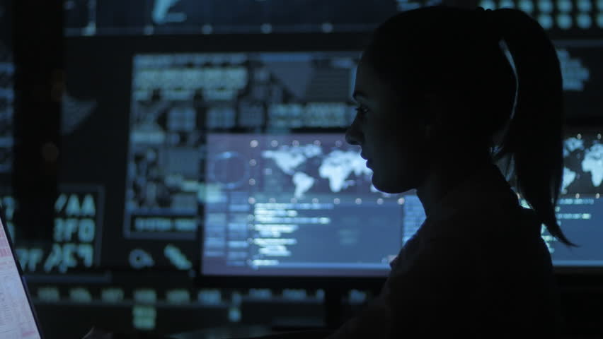 Silhouette of young woman IT programmer working at a computer in the data center filled with display screens   Shutterstock HD Video #1007866027