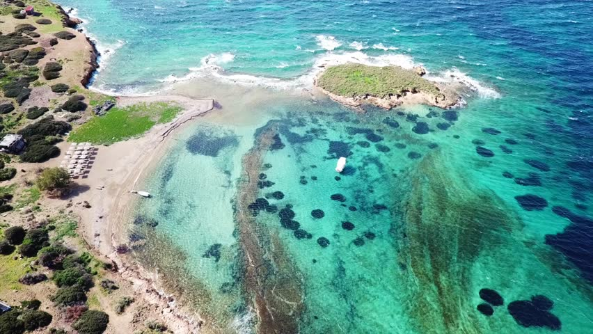 Aerial drone bird's eye view video of small islet of Ydrousa with turquoise and sapphire clear waters and only one mile distance from coast in Voula, Athens riviera, Attica, Greece