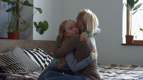 Charming adult mother caressing and comforting her crying cute teenage daughter while sitting on the bed in bedroom. Loving mom embracing and soothing her sad depressed little girl in domestic room.
