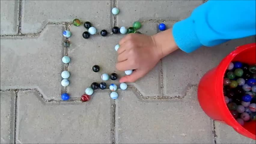 It's better than computer games children play in the garden the children gathering colored glass balls and marbles pouring around,