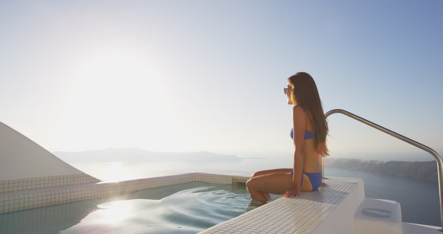 Luxury travel happy woman in bikini relaxing at the edge of swimming pool. Young Asian female is watching beautiful view of sunset. She is enjoying her vacation by sea. Santorini, Greece.
