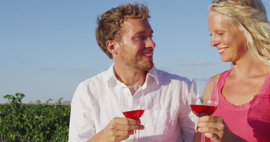 Couple drinking red rose wine toasting at vineyard. Romantic woman and man drinking red or rose wine smiling happy doing toast. Romantic lovers outside. Young Caucasian man and woman.