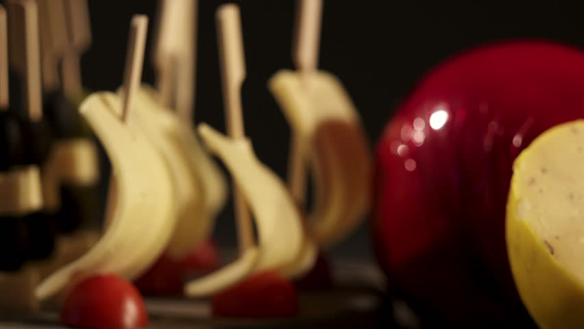 Edam cheese and wine tasting. Two glasses with red wine, grapes and cheese skewers on wooden table on a dark background. Dolly shot, high contrast