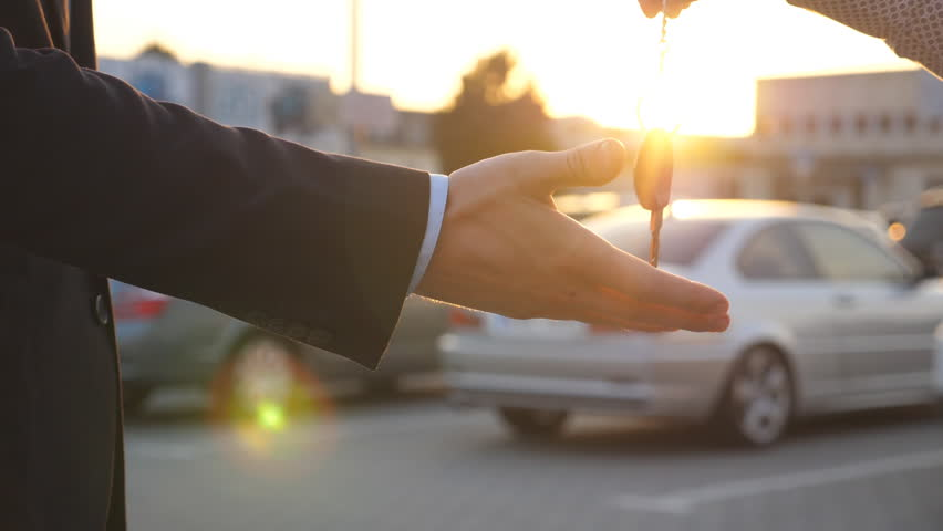 Male hands giving keys of car to his friend with sun flare at background. Arm of businessman passed car key. Handshake between two business men outdoor. Close up Slow motion