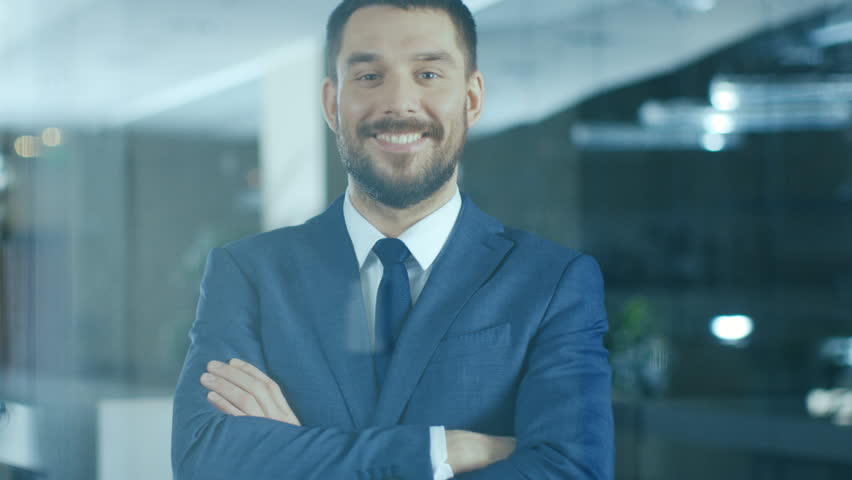 Successful Businessman Standing in the Office Smiles and Crosses Arms. Shot on RED EPIC-W 8K Helium Cinema Camera. | Shutterstock HD Video #1007931997