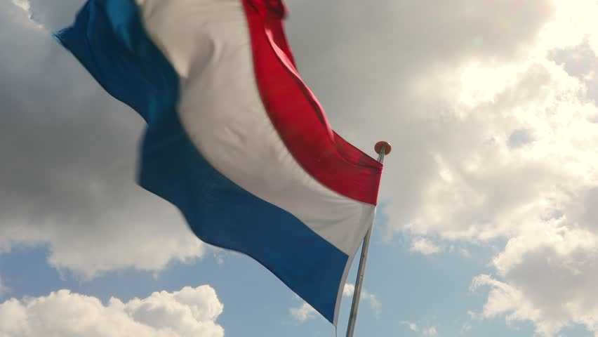 Flag of the Netherlands waving against blue sky in slow motion