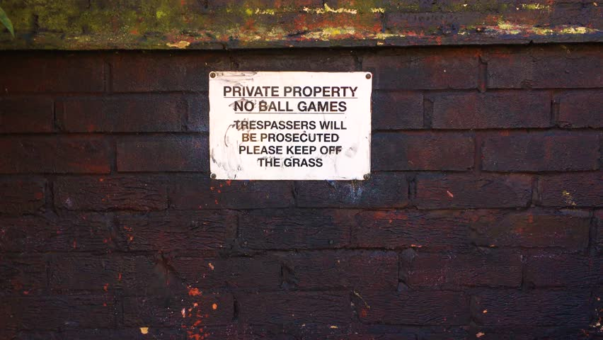 Private property. No ball games. Trespassers will be prosecuted. Please keep off the grass. Warning sign mounted onto a earth coloured brick wall with space for copy. Mitcham, England