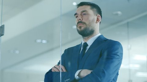 Handsome Businessman in the Suit Looks out of the Office Window. Successful Man on the Top of the World. Shot on RED EPIC-W 8K Helium Cinema Camera.