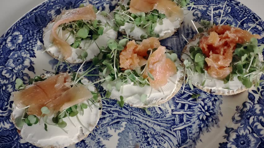 Putting pepper on healthy oatcake canapes with sprouts and white cheese. Hand picks up one sandwith from a blue plate