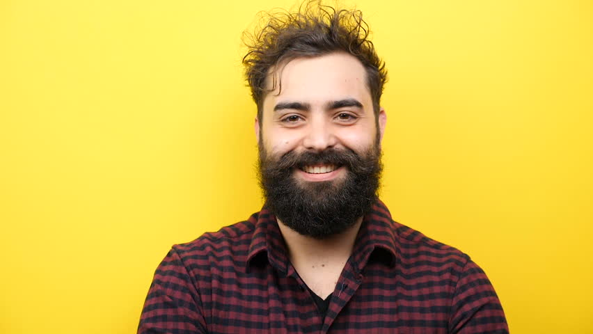 Slow motion of young bearded hipster rising his head up to the camera and smiling natural | Shutterstock HD Video #1007993137