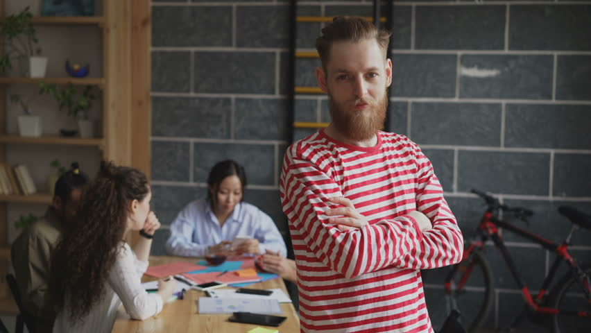 Portrait of young hipster male entrepreneur smiling and looking at camera while his colleagues working at modern loft office #1008026167