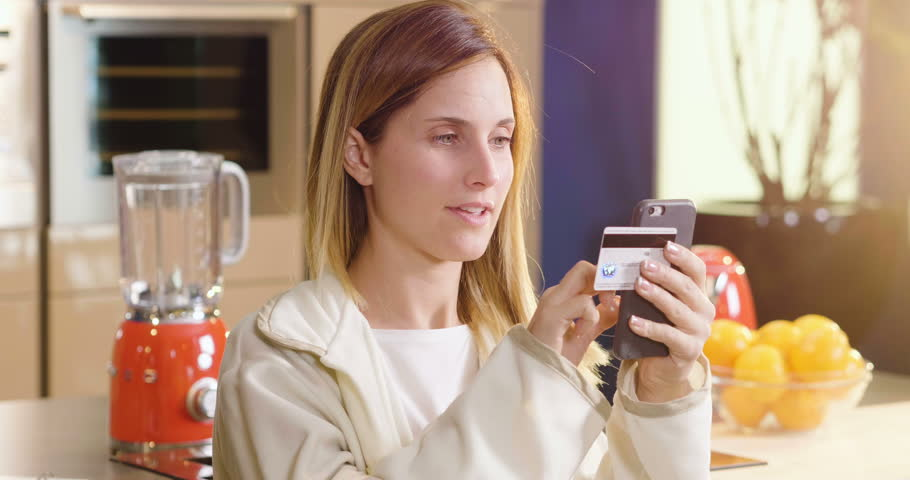 A woman at home is shopping online using the phone and entering credit card information. The woman is happy with her online purchases. Concept of: shopping, shipping, app and technology