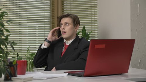 Young man in a suit sitting in the office, speaking on the phone, smartphone, sarcasm, tired. Work in the office concept 60 fps
