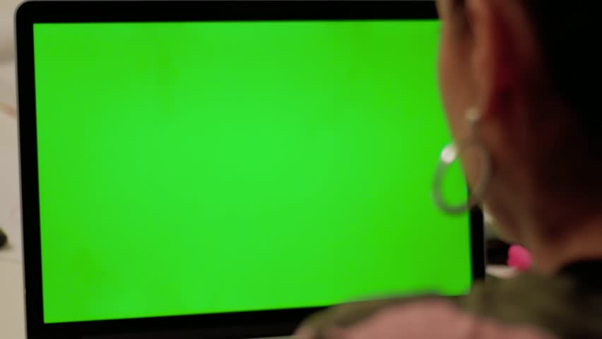 Girl in camouflage clothes makes video call on laptop with green screen. Concept of use chroma key gadget protective. Woman looks and talks at changeable display on computer. Person waste time online