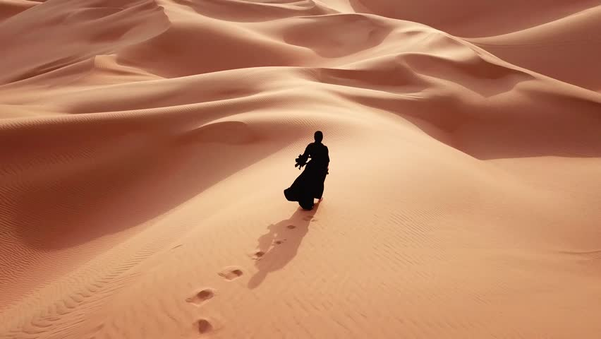 Young beautiful Caucasian woman walking in a traditional Emirati dress - abaya in Empty Quarter desert landscape. Abu Dhabi, UAE.