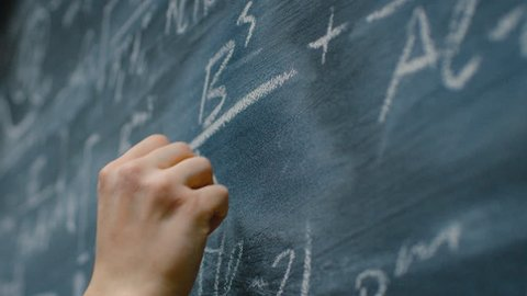 Hand Holding Chalk and Writing Complex and Sophisticated Mathematical Formula on the Blackboard. Underlining Equation. Shot on RED EPIC-W 8K Helium Cinema Camera.