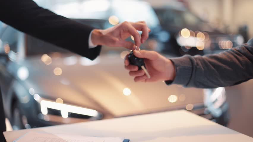 Young man giving keys of car to buyer. Men shaking hands in beautiful car dealership on background of bought cars.
