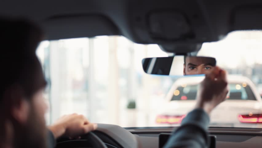 Man sitting at wheel of new car. Young handsome man with beard regulating and looking at rearview mirror.   Shutterstock HD Video #1008068107